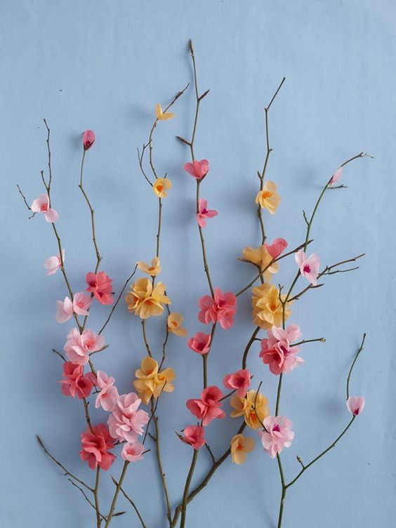 Papercraft. DIY Paper Blossom attached to branches on blue background: