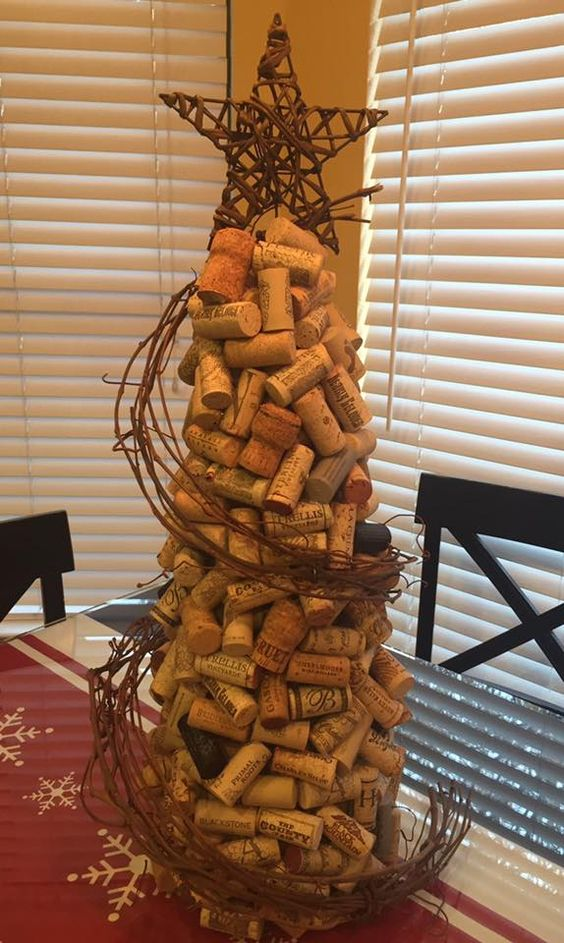 "This is my version of a wine cork Christmas tree. How I did it: I bought the tallest foam tree ""topiary"" from Michael's. I hot glued the corks on in 2 layers. 1st layer was very uniform. 2nd layer was more random. Got the grapevine garland at HL & soaked it in hot water for a few hours, then I made a tight ""wreath"" & zip-tied it together to dry. I wired it to the corks. Star came from the ""mini"" tree section @ HL. I straightened the wire base to stick into the foam tree. Merry Christmas! S"